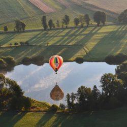 Heißluftballon spiegelt sich im See darunter