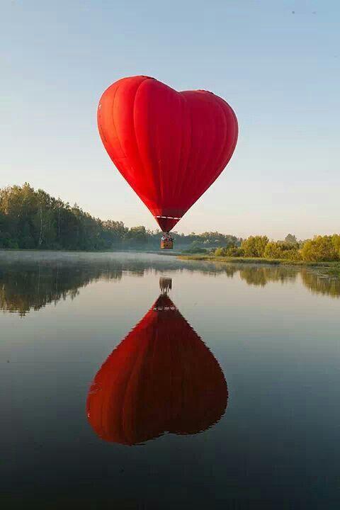 Heißluftballon in Herzform über einem See